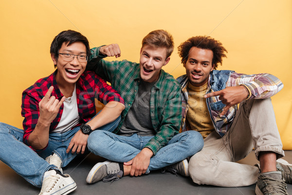 Three cheerful young men friends shouting and celebrating success Stock photo © deandrobot