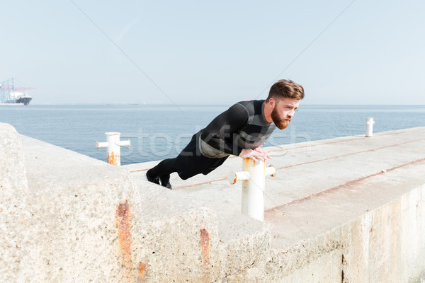 Man doing push ups near the sea Stock photo © deandrobot