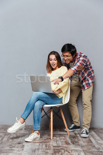 Full length portrait of a young multicultural couple with laptop Stock photo © deandrobot