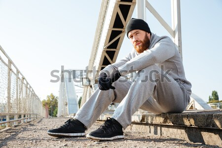 Sportsman in sports wear using mobile phone after workout Stock photo © deandrobot