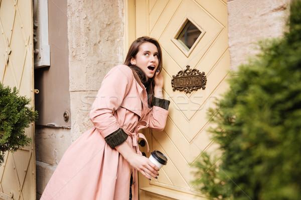 Model in coat evesdropping Stock photo © deandrobot