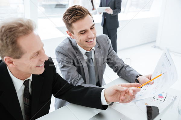 Бизнес-партнеры таблице коллеги изображение сидят документы Сток-фото © deandrobot