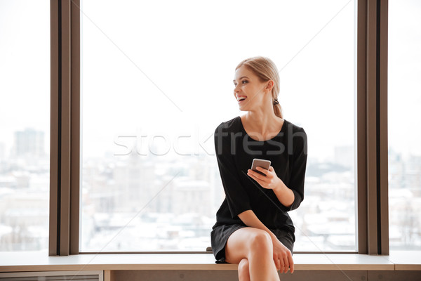 Woman worker in office near window chatting by phone. Stock photo © deandrobot