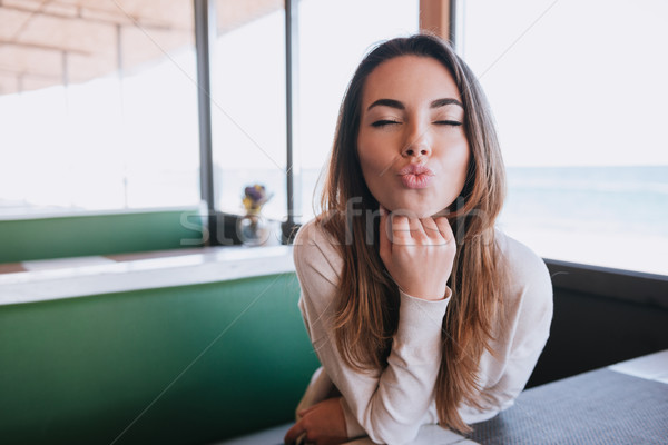 Woman on date in cafe sands air kiss Stock photo © deandrobot