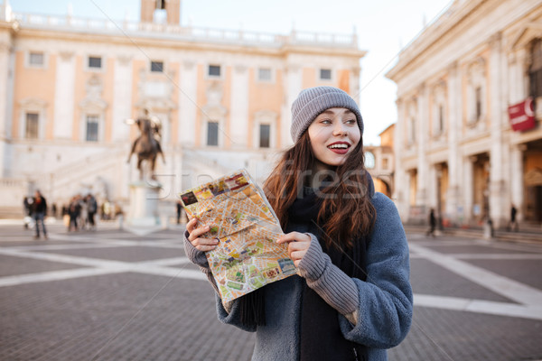 Cheerful woman with map standing in old city Stock photo © deandrobot