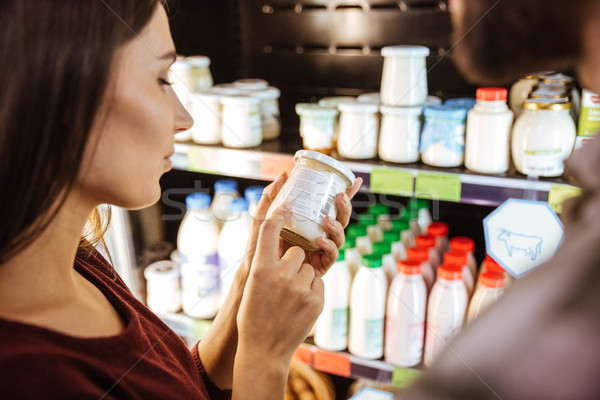 Beautiful young woman choosing milk product in grocery store Stock photo © deandrobot