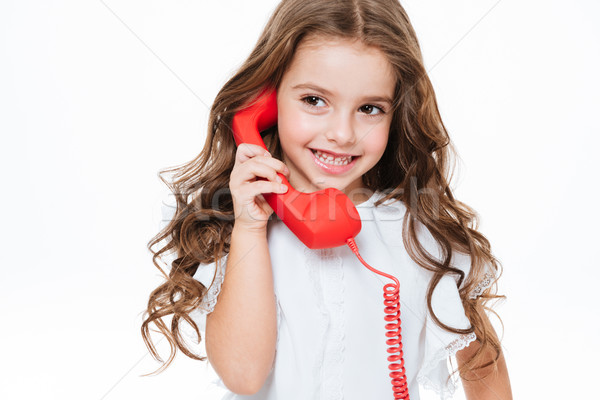 Cheerful cute little girl talking on red telephone Stock photo © deandrobot