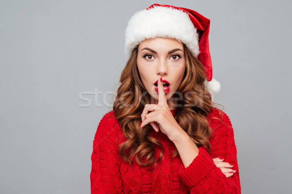 Beautiful young woman in santa hat showing silence gesture Stock photo © deandrobot