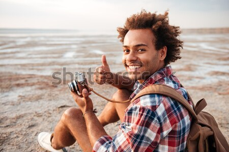 Cheerful african man taking pictures with vintage camera on beach Stock photo © deandrobot