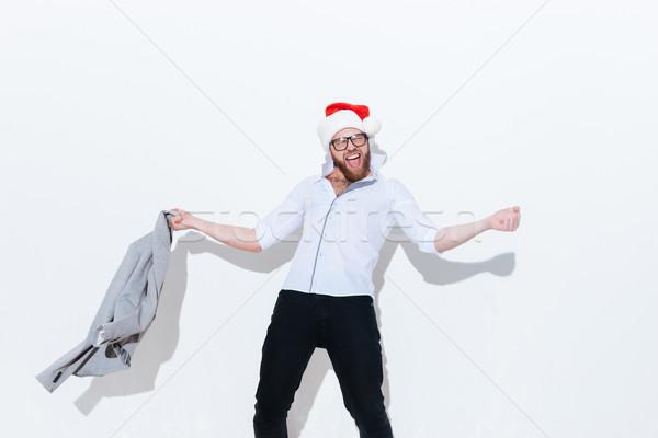 Boldog izgatott fiatalember mikulás kalap szórakozás Stock fotó © deandrobot