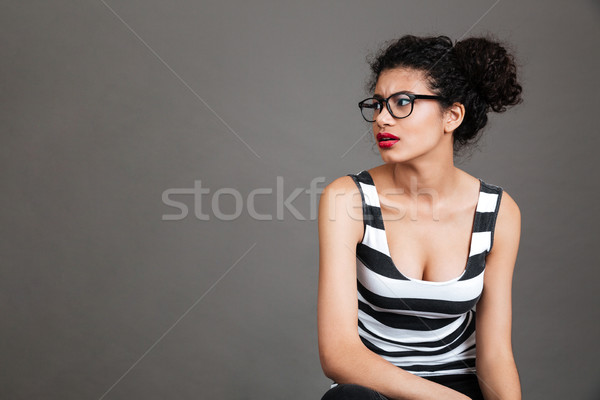 Serious frowning african woman in glasses sitting and looking away Stock photo © deandrobot