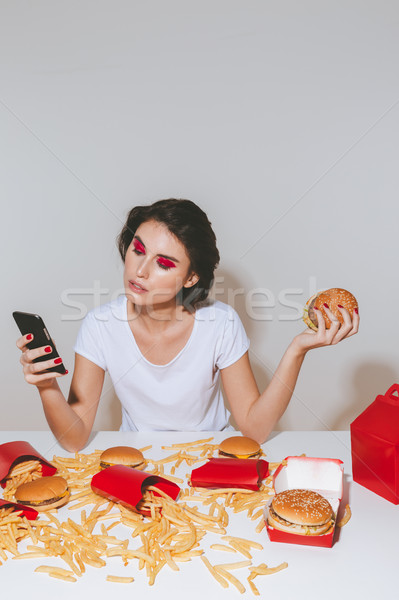 Pretty young woman with hamburger sitting and using mobile phone Stock photo © deandrobot