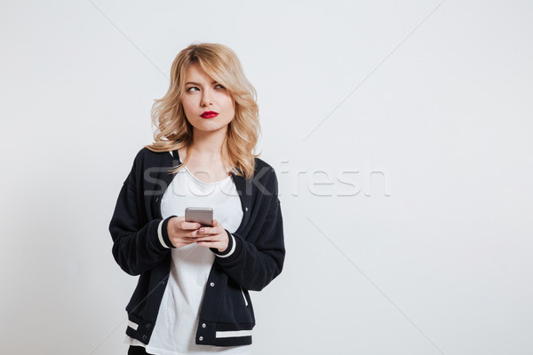 Casual pensive woman holding mobile phone and looking away Stock photo © deandrobot
