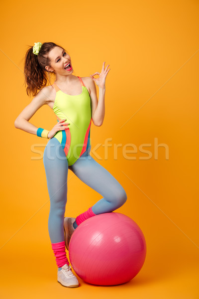 Young fitness woman posing over yellow background make okay gesture. Stock photo © deandrobot