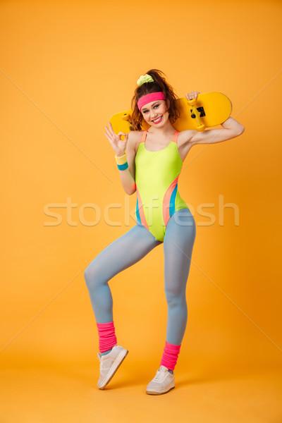 Mosolyog fiatal nő atléta tart gördeszka mutat Stock fotó © deandrobot