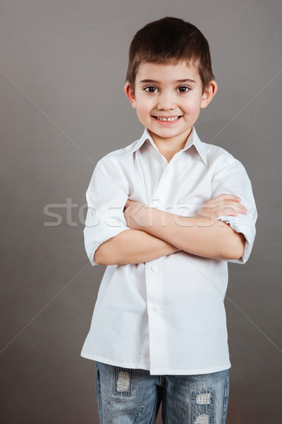 Smiling little boy in white shirt standing with arms crossed Stock photo © deandrobot