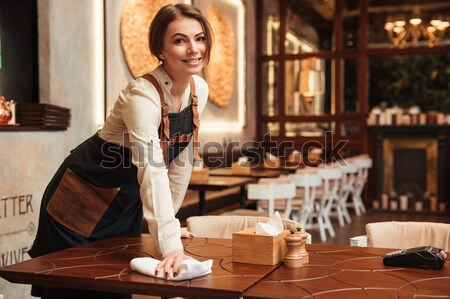 Young woman waiter standing in cafe. Looking aside. Stock photo © deandrobot