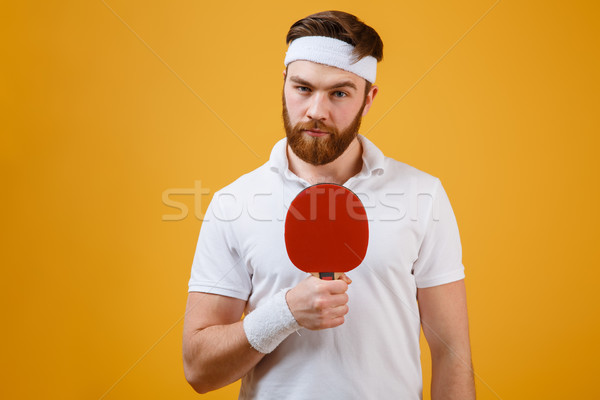 Handsome young sportsman holding racket for table tennis Stock photo © deandrobot