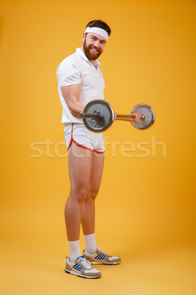 Smiling bearded fitnes man doing workout with barbell Stock photo © deandrobot