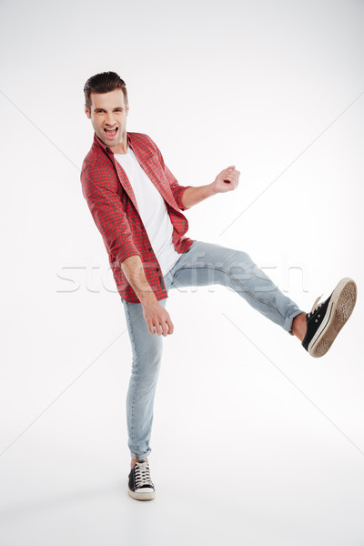 Vertical image of man playing on imaginary guitar Stock photo © deandrobot