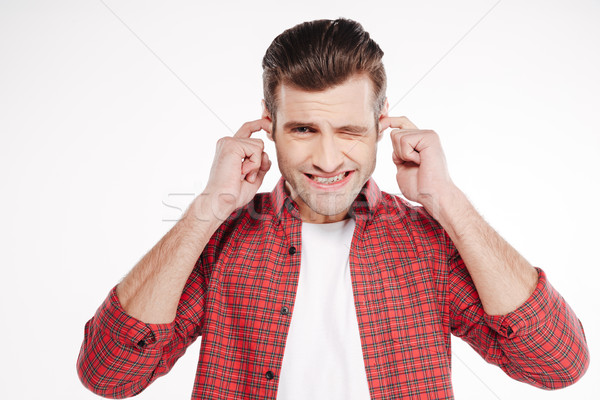 Young man covering his ears Stock photo © deandrobot