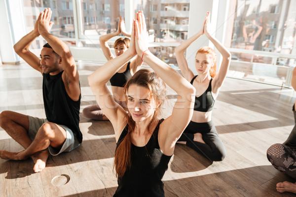 Grupo de personas sesión loto plantean yoga estudio Foto stock © deandrobot