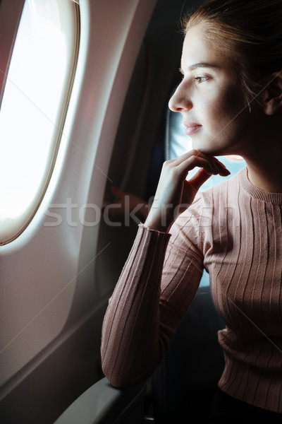 Vertical image of woman in aircraft Stock photo © deandrobot