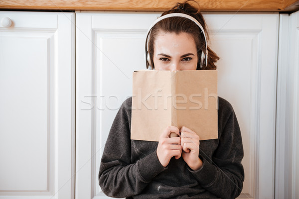 Young pretty girl in headphones covering face with book Stock photo © deandrobot