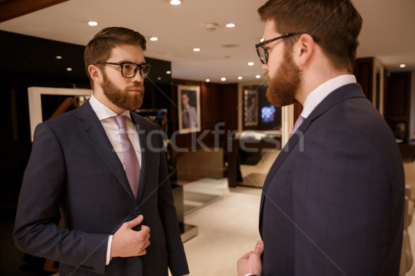 Serious young bearded businessman standing indoors. Stock photo © deandrobot