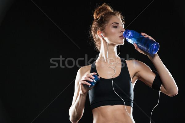 Mujer de la aptitud agua potable estudio negro mano fitness Foto stock © deandrobot