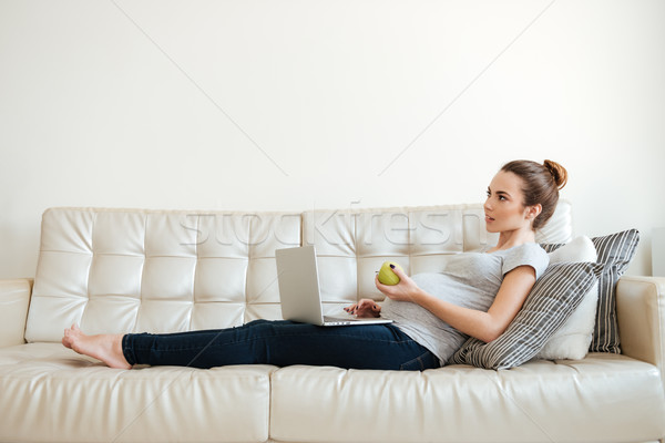 Pensive pregnant young woman thinking and using laptop on sofa Stock photo © deandrobot