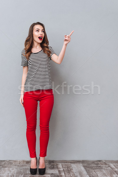 Full length portrait of Young surprised woman pointing away Stock photo © deandrobot