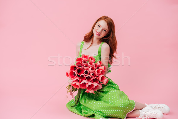 Uśmiechnięty imbir kobieta posiedzenia piętrze bukiet Zdjęcia stock © deandrobot