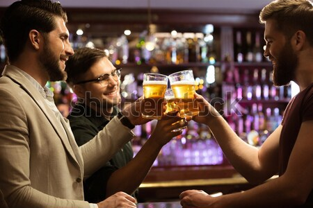 Relaxed young man drinking glass of beer Stock photo © deandrobot