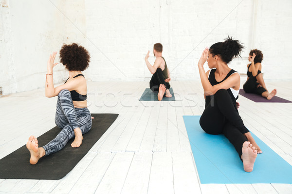 Group of people doing yoga in gym sitting on training mats Stock photo © deandrobot