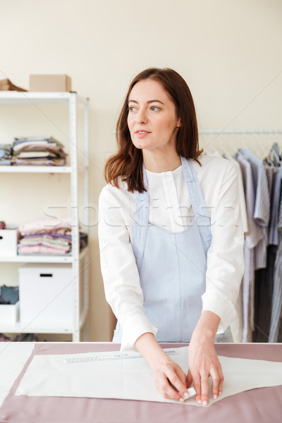 Young serious woman seamstress looking aside Stock photo © deandrobot