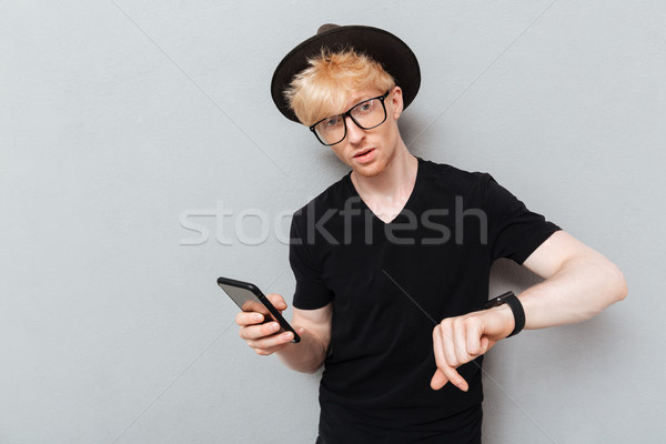 Caucasian man using his watch and mobile phone. Stock photo © deandrobot