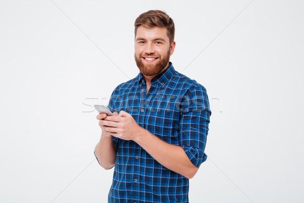 Tevreden bebaarde man shirt smartphone Stockfoto © deandrobot