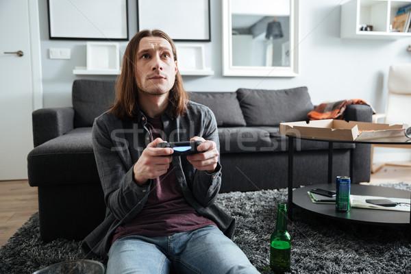 Concentrado hombre sesión casa jugar Foto stock © deandrobot