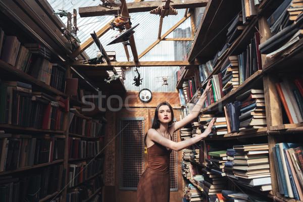 Young brunette girl standing among books Stock photo © deandrobot