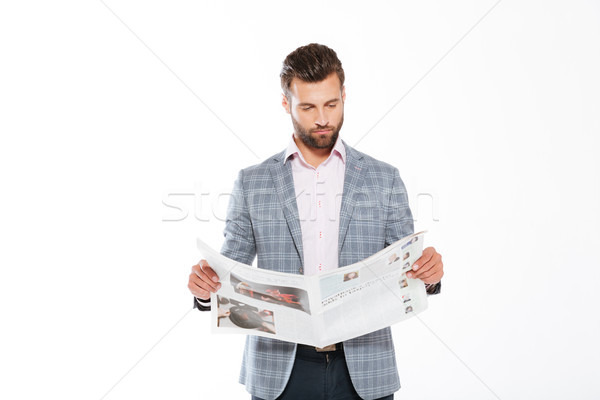 Concentrated young man reading gazette Stock photo © deandrobot