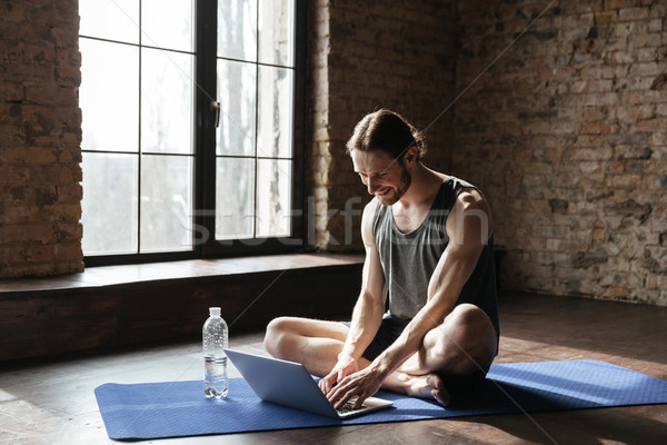 Handsome strong sportsman sitting near bottle of water using laptop Stock photo © deandrobot