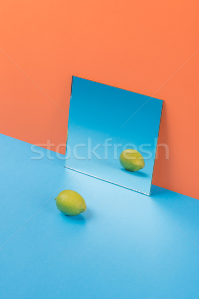 Lime on blue table isolated over orange background Stock photo © deandrobot