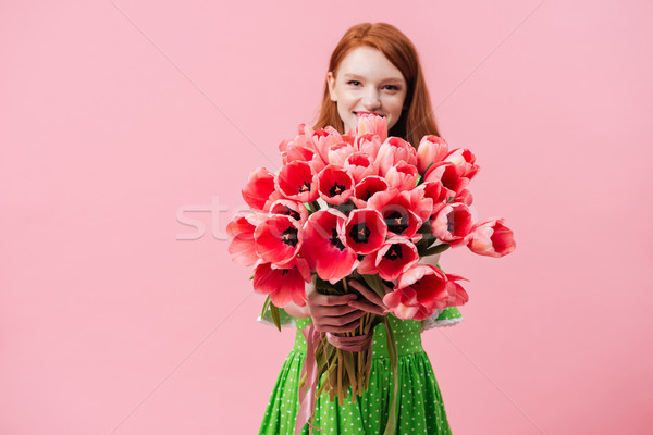 Positive girl holding tulips Stock photo © deandrobot