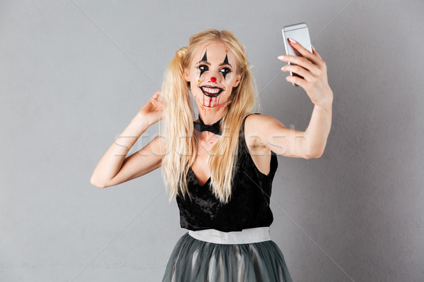 Glimlachend blonde vrouw halloween make-up smartphone Stockfoto © deandrobot