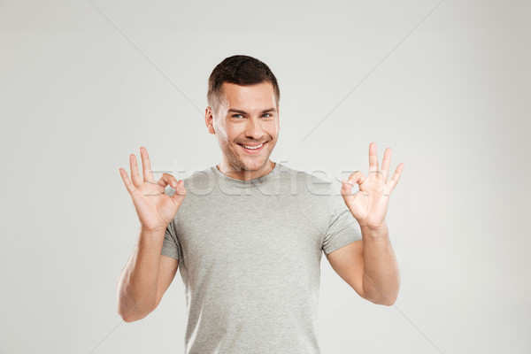 Happy young man showing okay gesture. Looking at camera. Stock photo © deandrobot