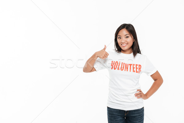 Portrait of a happy satisfied asian woman in volunteer t-shirt Stock photo © deandrobot