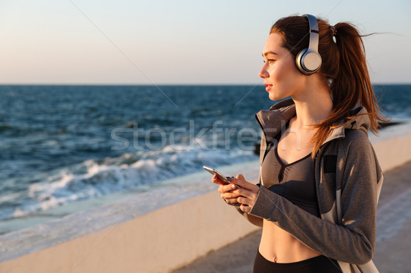 Photo of young brunette sport woman listening to music in gray h Stock photo © deandrobot