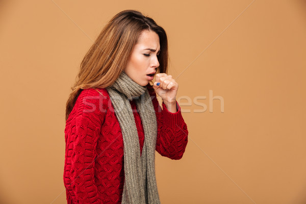 Photo of young coughing brunette woman in warm wear Stock photo © deandrobot