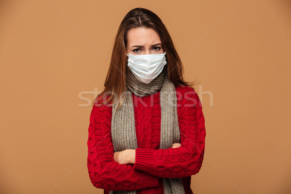 Sick woman in protective mask standing with crossed hands, looki Stock photo © deandrobot